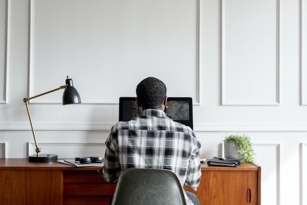 a man (seen from behind) sitting at a wooden desk topped with a lamp, notebooks, a plant, and over-the-ear headphones using a computer to access online therapy.