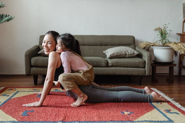 A woman doing yoga as her child plays on her back, perhaps to deal with attachment anxiety, or feeling anxious about being away from each other..