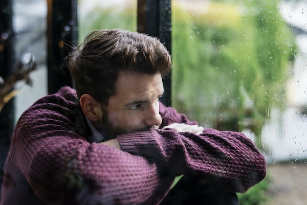 grief stages - man staring out window