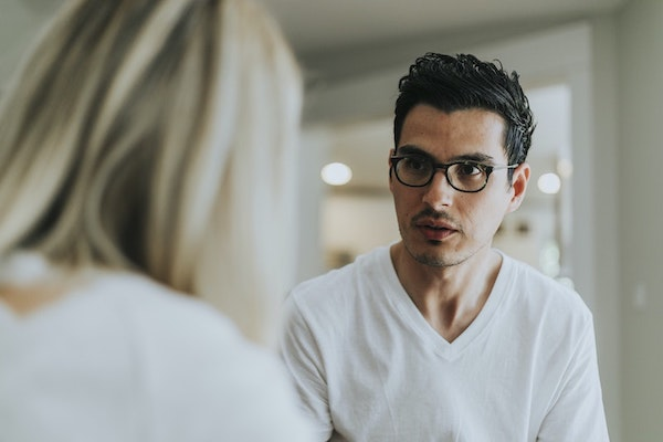 man with dark hair in glasses looking at blonde woman