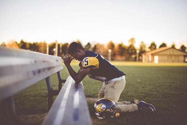 football player kneeling down on bench outside