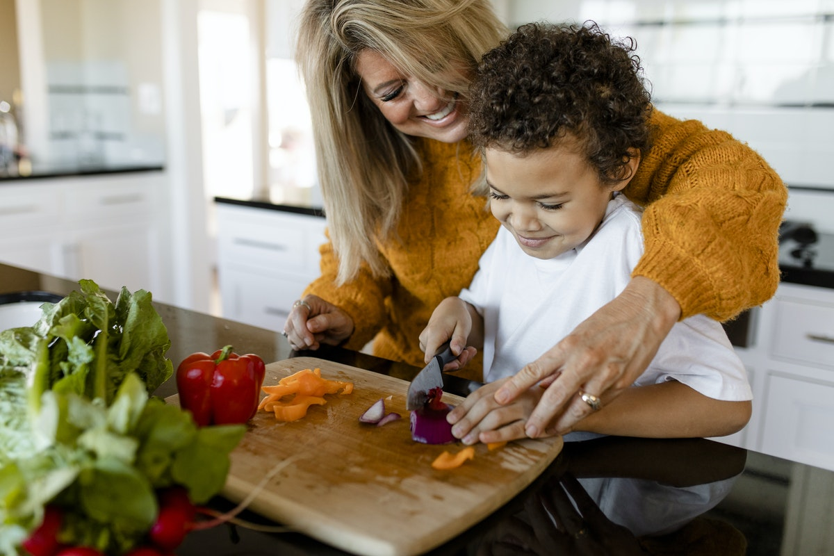 Parent helping kid cook lunch