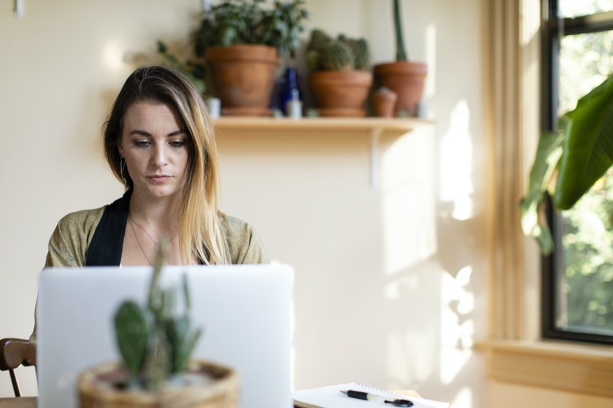 A woman sits in her sunny kitchen with her laptop, researching online therapy options.