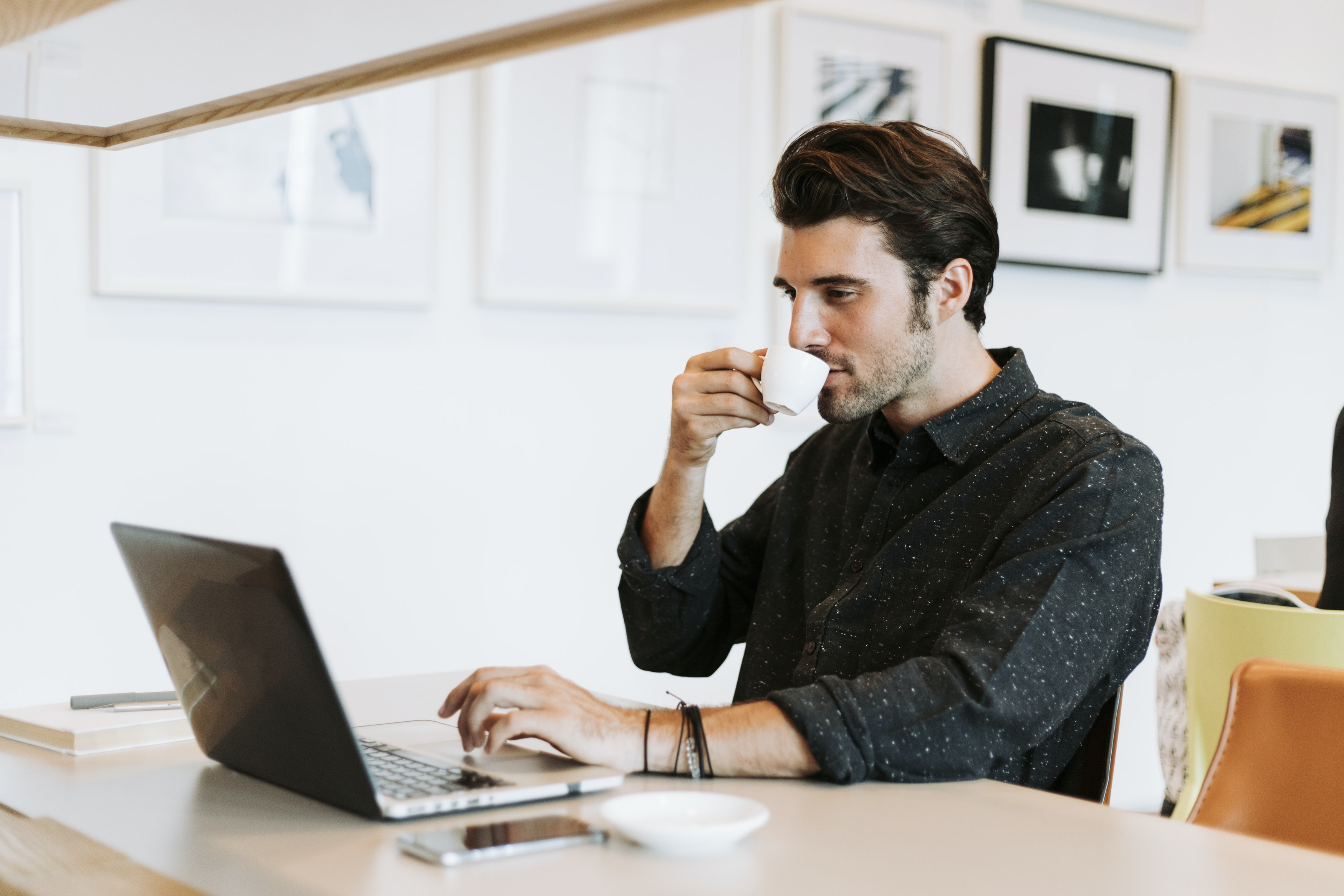 A man sips espresso by his laptop, preparing for his online counseling session.