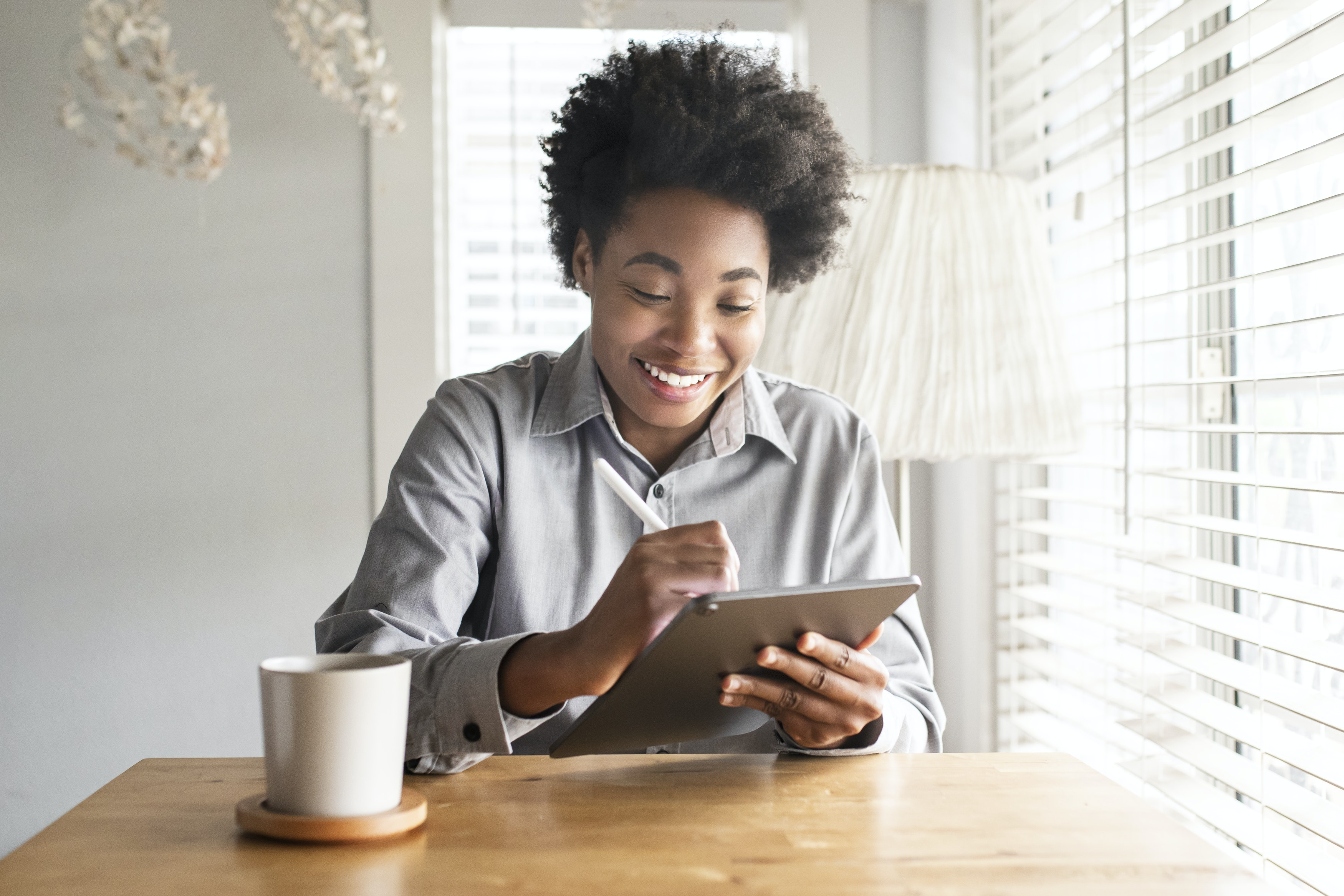 A woman smiles at her therapist while they have an online therapy session.