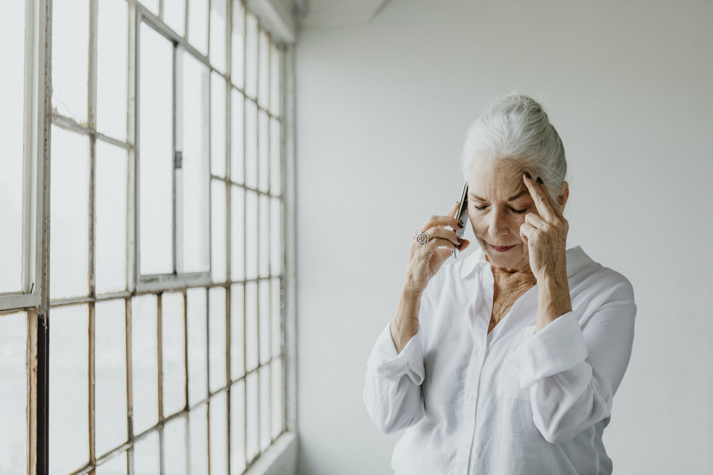 frowning woman with white hair places fingers on her forehead in frustration while holding a cell phone to her ear