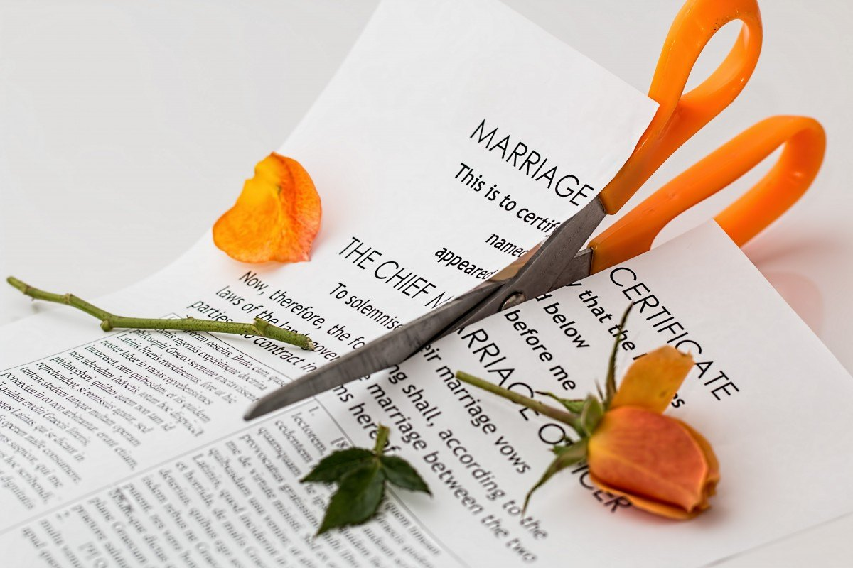 A broken marriage certificate is pictured with a rose cut in two.