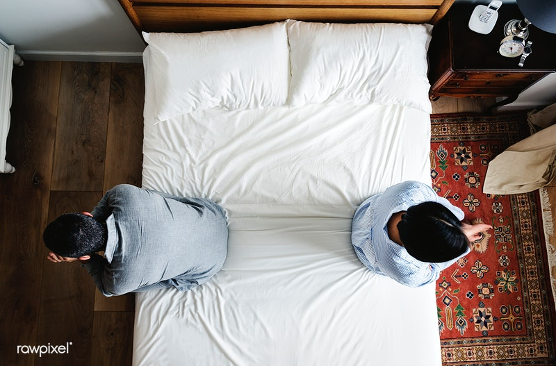 A couple is pictured seated on opposite sides of a bed, pondering how to fix a broken marriage.