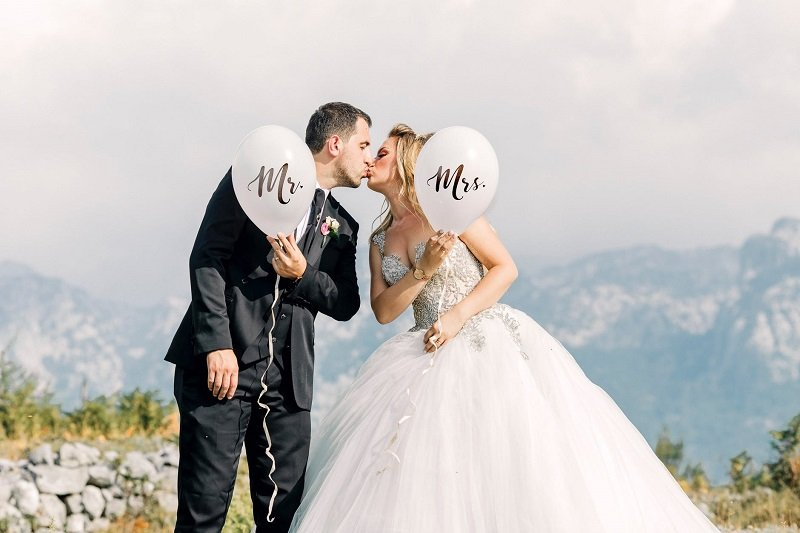 A married couple holding balloons with Mr. and Mrs. written on them kisses on a mountaintop.