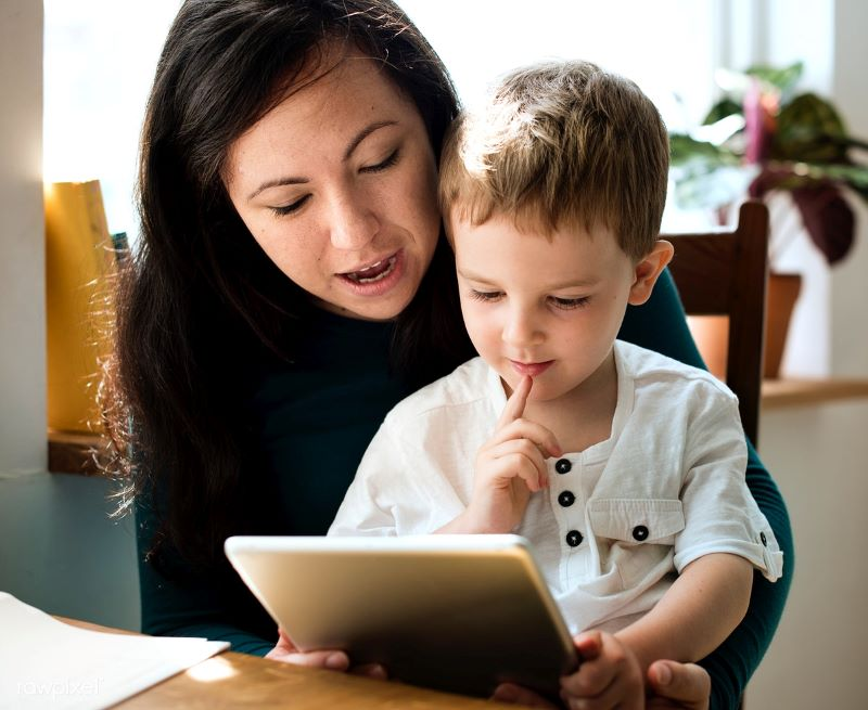 Authoritative parenting examples: a mother reads with her son, and asks him questions to make sure he understands the reading while respecting his own opinions.