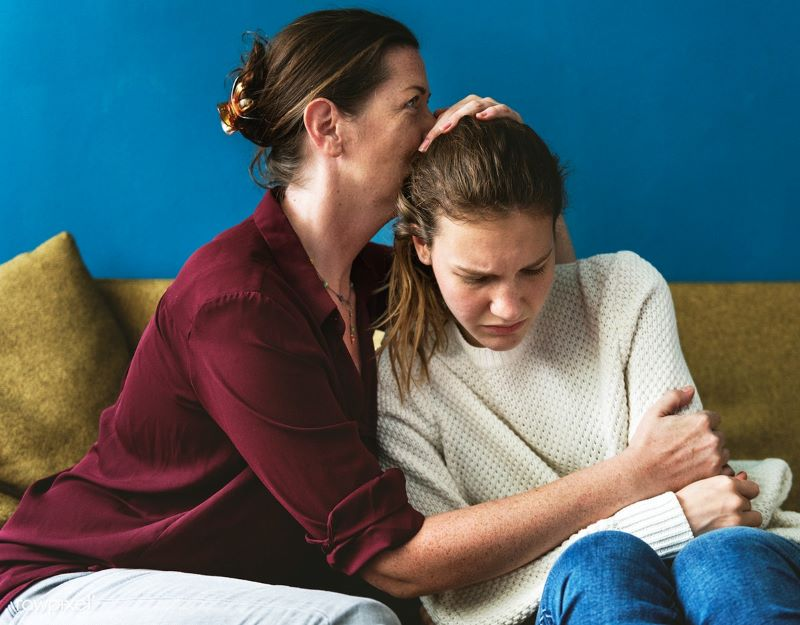 Permissive parenting examples: a mom hugs her child and doesn't let her experience any challenges in life.