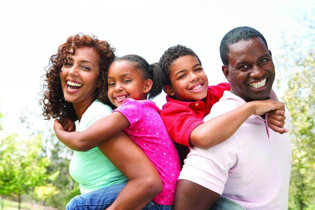 A family of four laughs together outside, an example of healthy parenting.