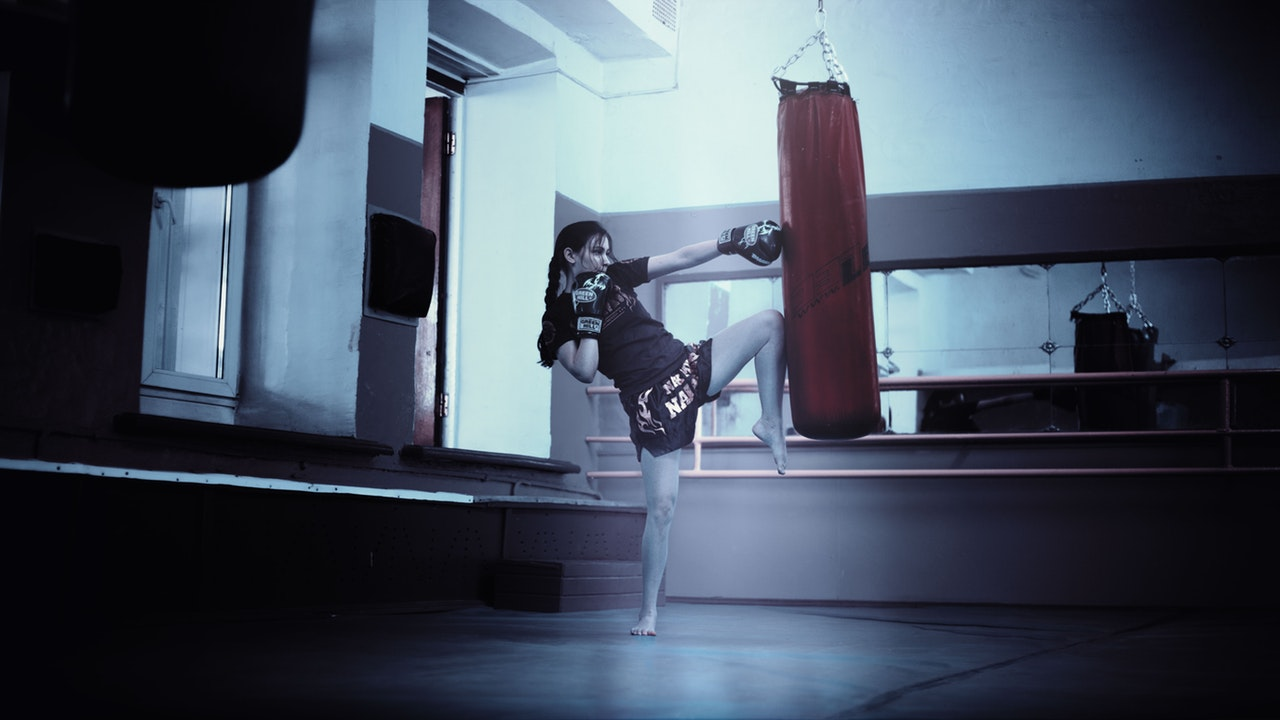 A woman kickboxing, to release anger in beneficial ways, and show how to release anger without harming yourself or others; in other words, she allows her anger to be released.