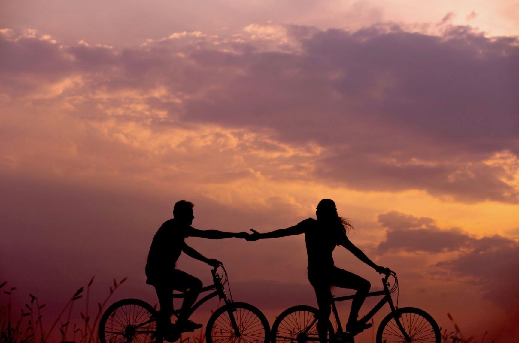 A couple rides bikes and holds hands against a beautiful orange sunset.
