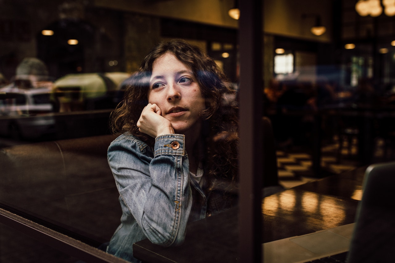 A woman looks out the window of a coffee shop.