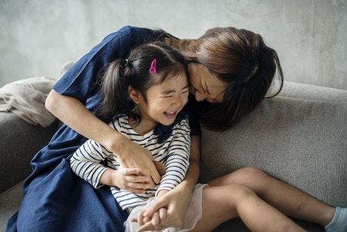 Authoritative parent tickling her daughter
