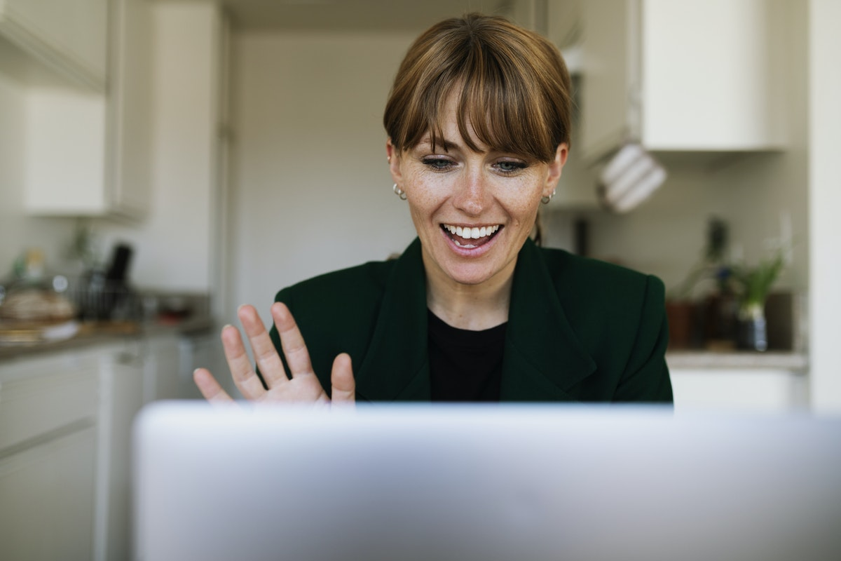 A woman smiles at her licensed online counselor, and waves hello as they begin her session.